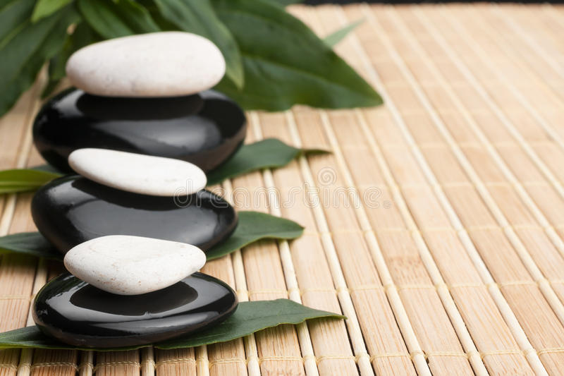 Spa concept with zen stones and leaves. In the background mat stock photos