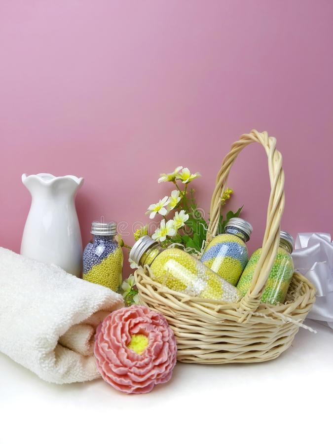 Spa cosmetic bottles in basket and bath treatment on white table over pink background stock photography