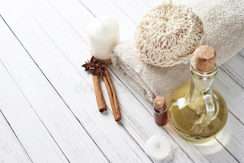 Spa and cosmetic treatment composition. Candles, massage oil and towel on white background stock images