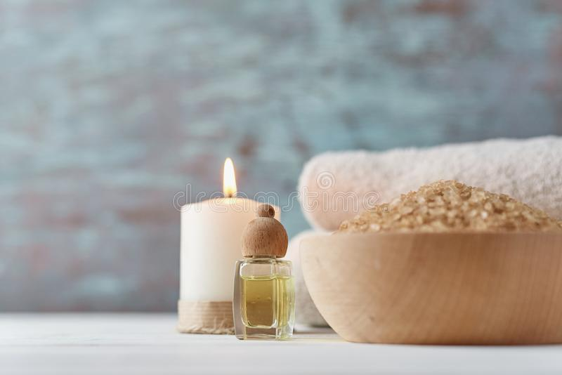 Spa and cosmetic treatment composition. With copy space. Sea salt in bowl, burning candle and towels royalty free stock photo