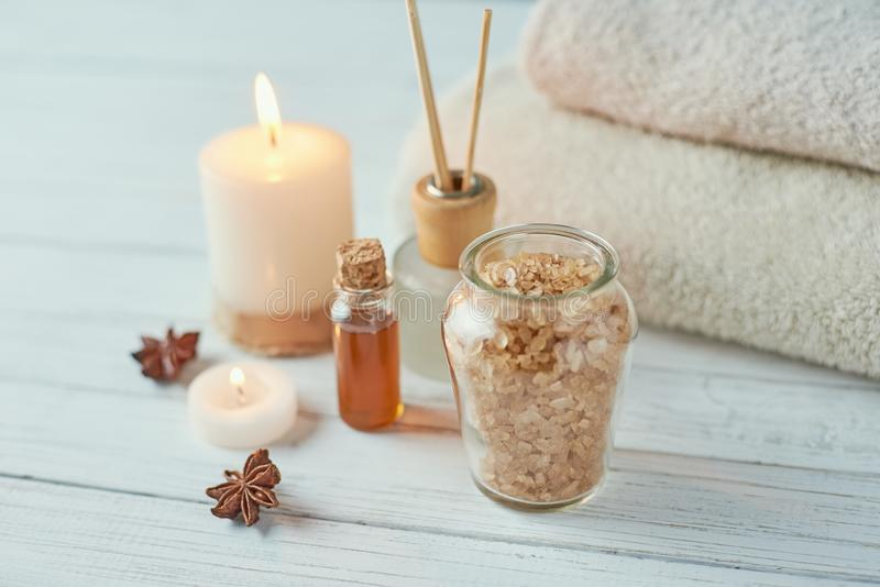 Spa and cosmetic treatment composition. Sea salt in bowl, burning candle and towels royalty free stock photography