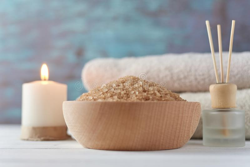 Spa and cosmetic treatment composition. With copy space. Sea salt in bowl, burning candle and towels royalty free stock photography