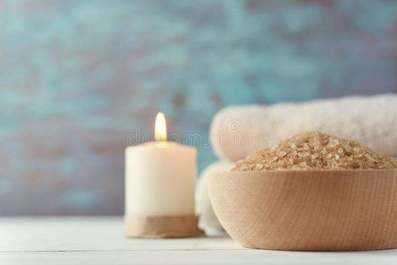Spa and cosmetic treatment composition. With copy space. Sea salt in bowl, burning candle and towels stock photos