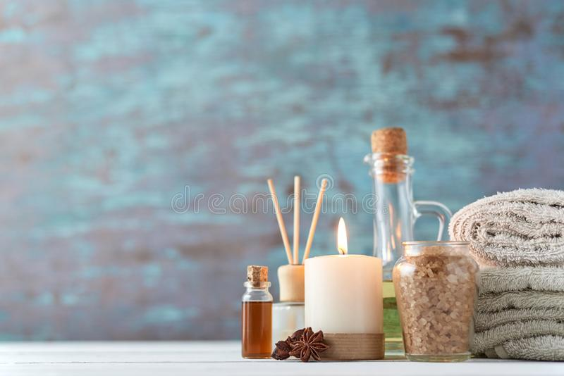 Spa and cosmetic treatment composition. With copy space. Sea salt, burning candle and towels royalty free stock image