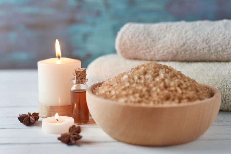 Spa and cosmetic treatment composition. Sea salt in bowl, burning candle and towels stock images