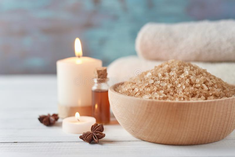 Spa and cosmetic treatment composition. Sea salt in bowl, burning candle and towels stock photo
