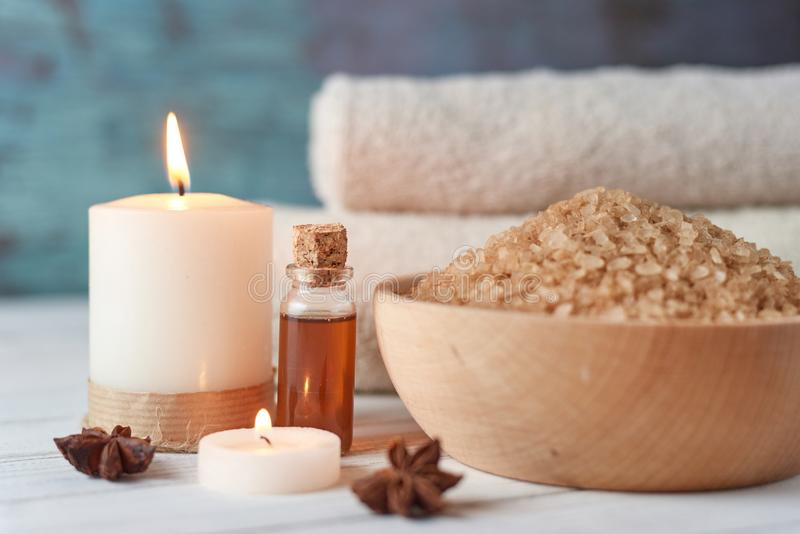 Spa and cosmetic treatment composition. Sea salt in bowl, burning candle and towels royalty free stock image