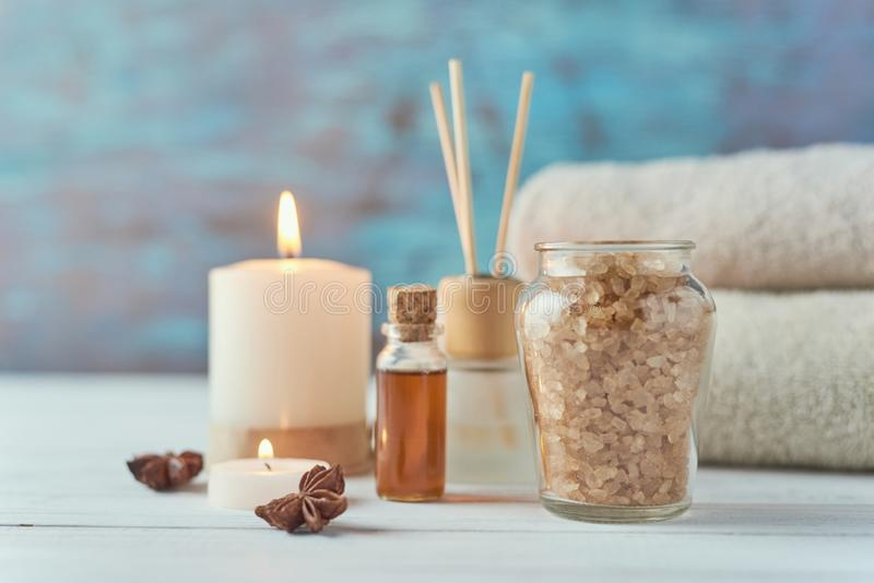Spa and cosmetic treatment composition. Sea salt, burning candle and towels royalty free stock images