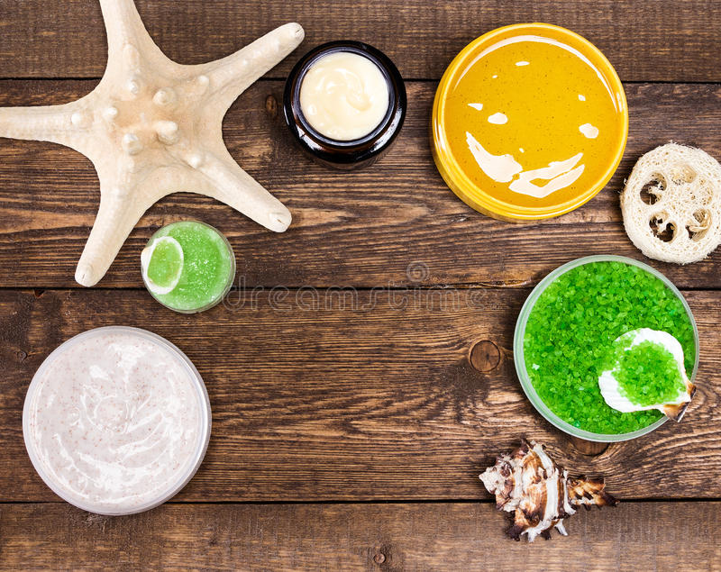 Spa cosmetics and accessories frame. Spa cosmetics and accessories: sea salt, loofah, skin care cream, natural scrubs with shells and starfish on wooden planks royalty free stock image