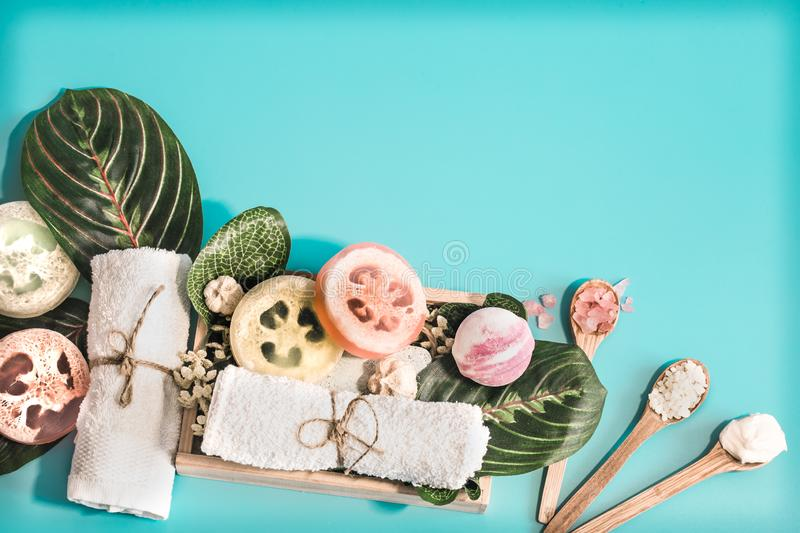 Spa cosmetics, composition on a blue background. Organic Spa cosmetics, composition with soap and Spa care items on blue background with tropical leaf, Spa and royalty free stock image