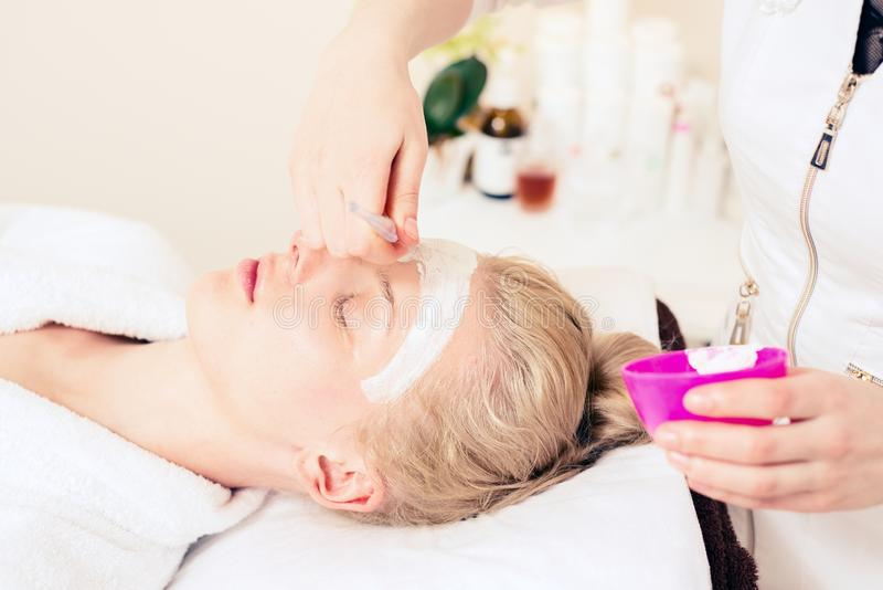 Spa cosmetology. doctor cosmetologist applies cream to face. girl caring for skin. healthy skin concept royalty free stock image