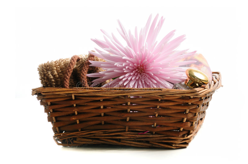 Spa elements in a basket. Basket with natural spa elements and pink flower isolated stock photography