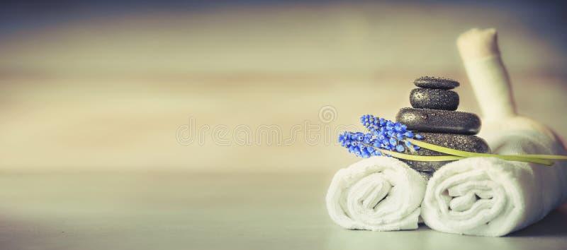 Spa eller wellnessinställning med massageutrustning och blommor, främre sikt arkivbilder