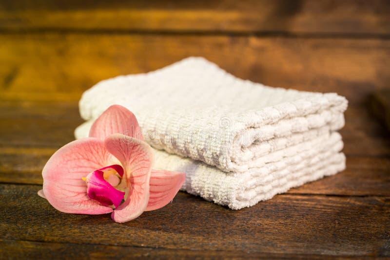 Spa eller wellnessuppsättning Vit handduk- och rosa färgblommalilja på brunt royaltyfri foto