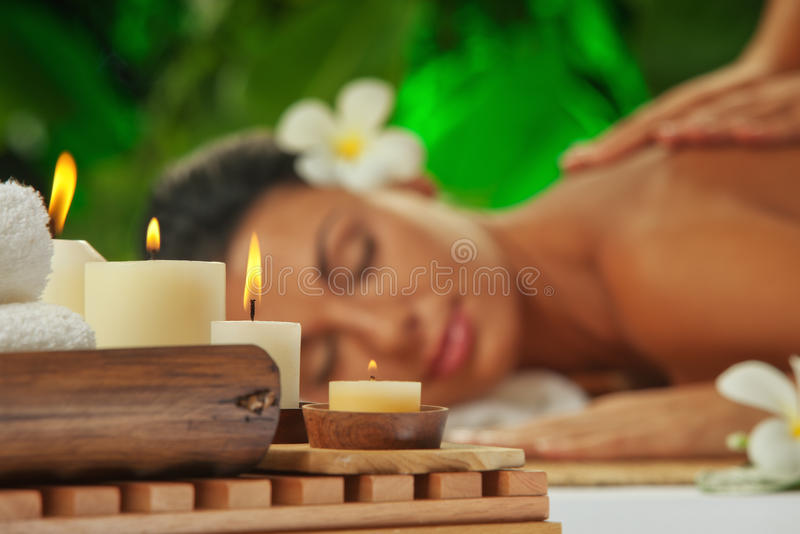 Spa. focused on candles. Portrait of young beautiful woman in spa environment. focused on candles royalty free stock photos