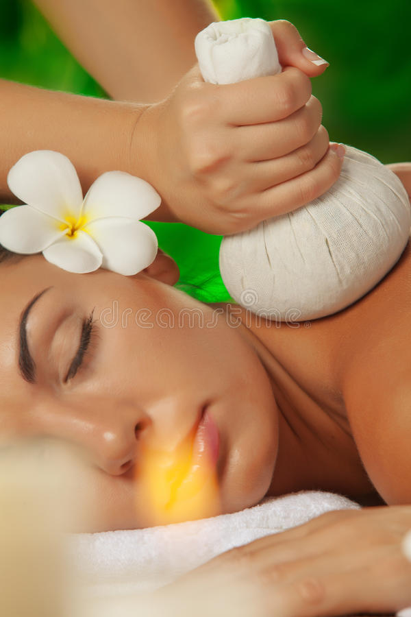 Spa fragment. Portrait of young beautiful woman in spa environment. focused on candles royalty free stock photography
