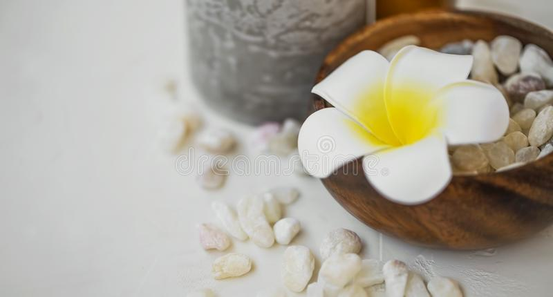 Spa frangipani flower on bamboo bowl with bath salt and candle, spa still life and wellness setting. Beauty and relax spa background stock photography