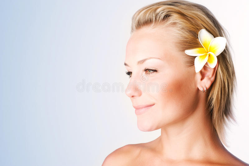 Spa Girl. Beautiful Healthy Young Woman with frangipani flower royalty free stock image
