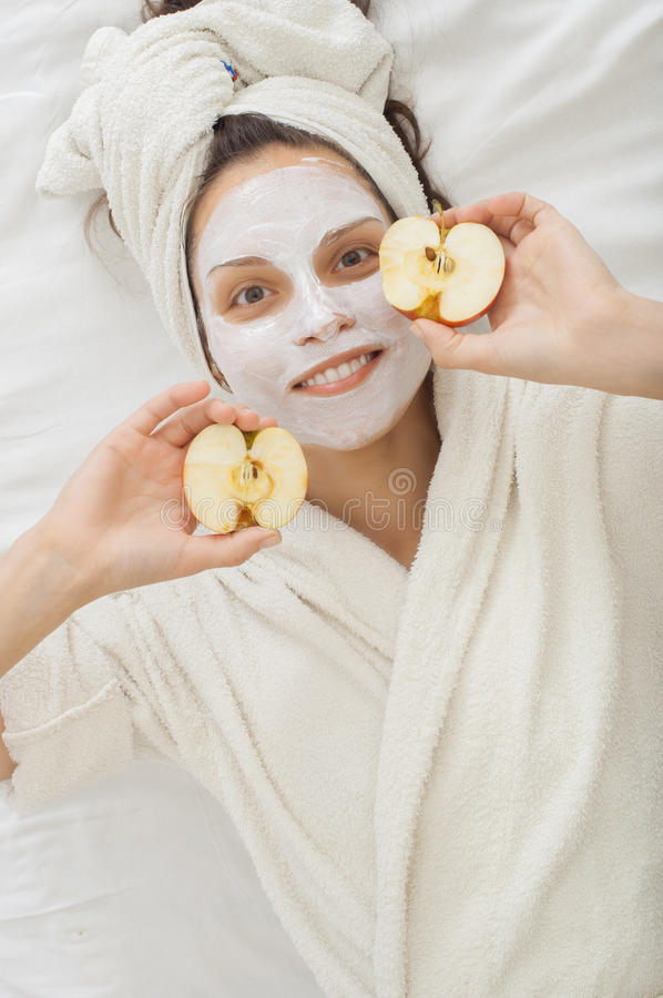 Spa girl in a white coat with the halves of the apple stock photography