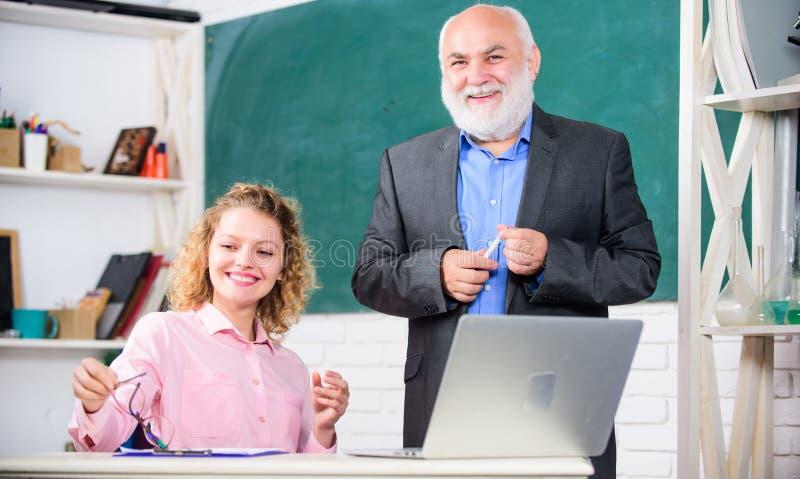 Spa? haben zusammen Student und Tutor mit Laptop glückliches Studentenmädchen mit Tutormann an der Tafel Bestehen Sie Pr?fung leh lizenzfreies stockbild