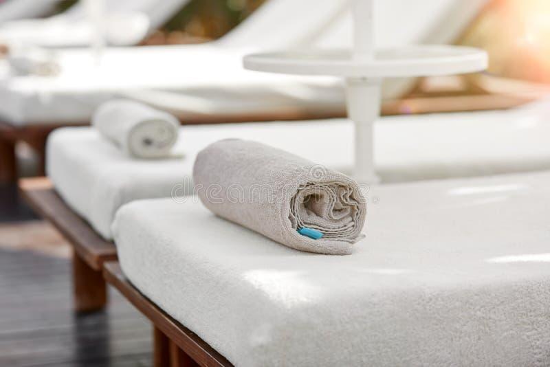 Spa handduk på sunbed nära simbassängen arkivfoton