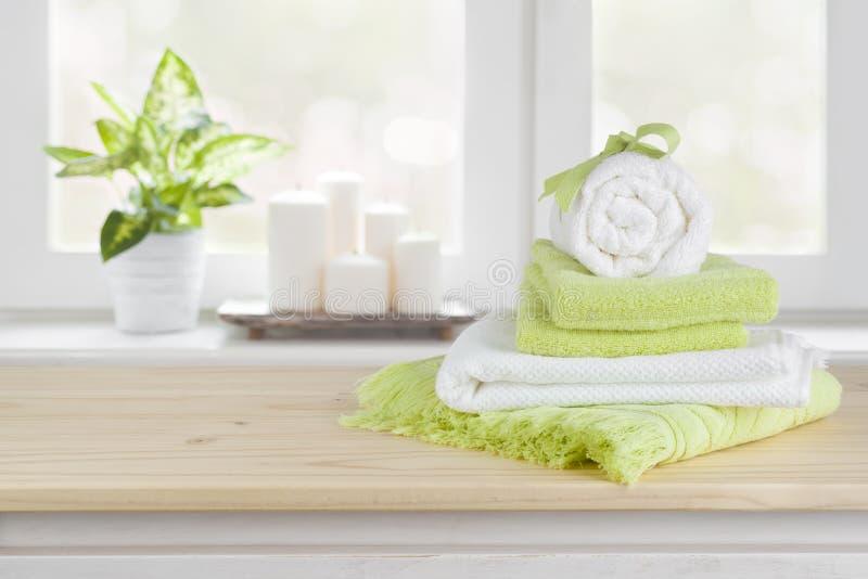 Spa handdukar på trätabellen över suddig salongfönsterbakgrund arkivbilder