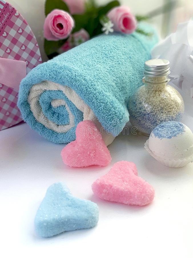 Spa handmade cosmetic products. Towels, soap, cream jar, scrub shape of heart on white background. stock images
