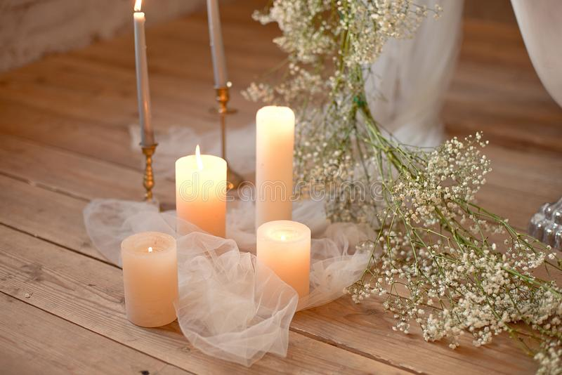 Spa, health, beauty and wellness concept with rose petals scattered around burning candles on a wooden floor in a high. Angle view royalty free stock photo