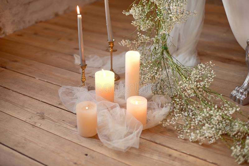 Spa, health, beauty and wellness concept with rose petals scattered around burning candles on a wooden floor in a high. Angle view royalty free stock photos
