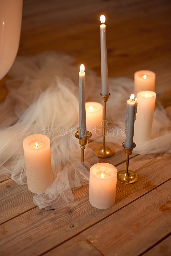 Spa, health, beauty and wellness concept with rose petals scattered around burning candles on a wooden floor in a high. Angle view royalty free stock image