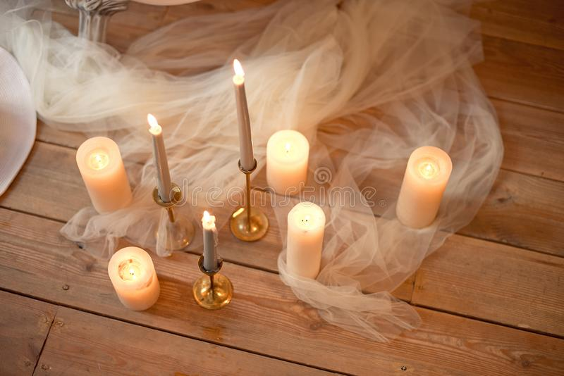 Spa, health, beauty and wellness concept with rose petals scattered around burning candles on a wooden floor in a high. Angle view royalty free stock photography