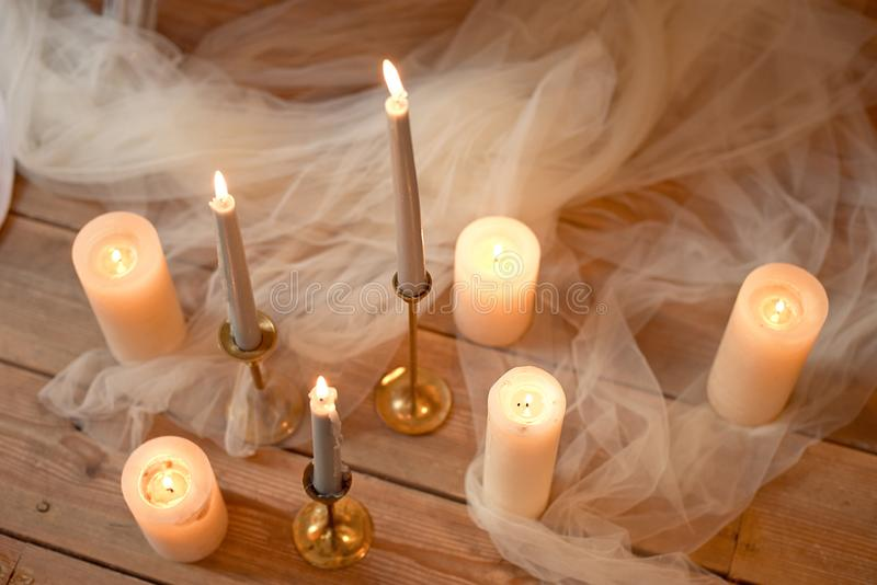 Spa, health, beauty and wellness concept with rose petals scattered around burning candles on a wooden floor in a high. Angle view stock photos