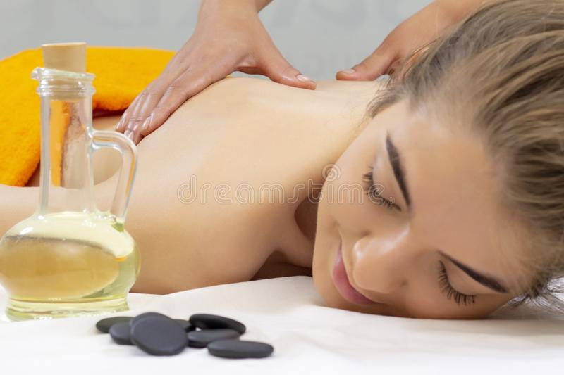 Spa hot stone massage. Attractive beautiful girl lying on massage bed in spa salon Spa aroma therapy and beauty treatments concept stock photo
