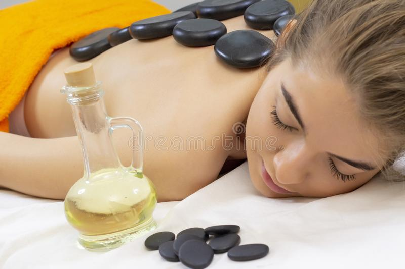 Spa hot stone massage. Professional beautician massaging female back by stones. stock photos