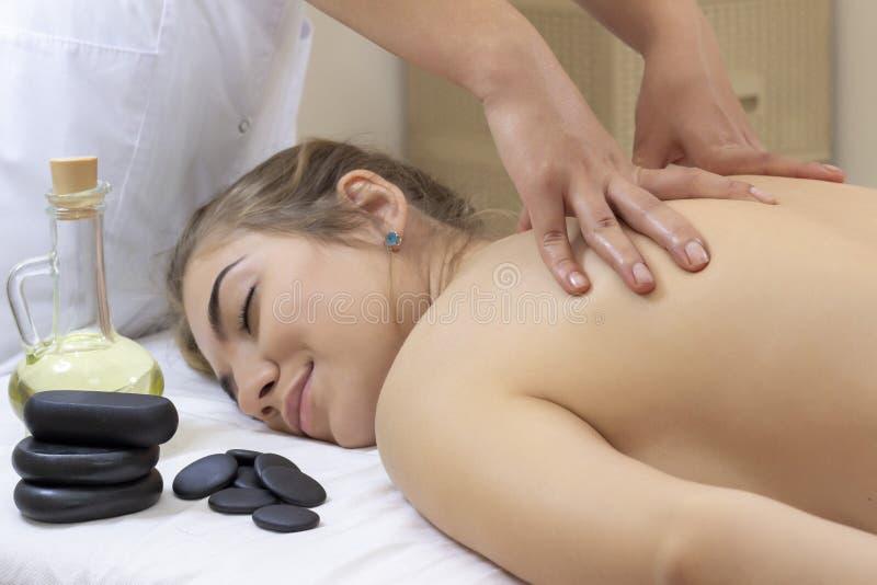 Spa Hot Stone Massage. Stone treatment. Woman getting a hot stone massage at a day spa. stock photos