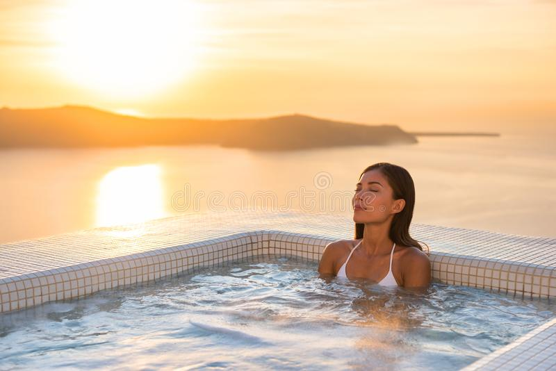 Spa hotelllyx kopplar av bubbelpoolterapipölen som den asiatiska kvinnan som kopplar av i den varma semesterorten, badar yttersid royaltyfri bild
