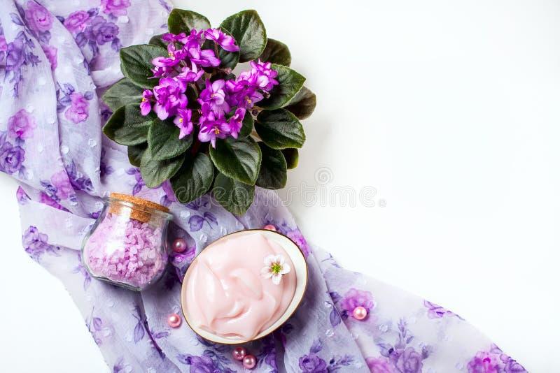 Spa inställning med skönhetsmedelkräm, salt för bad och afrikansk violet i blomkruka på vit trätabellbakgrund Selektivt fokusera royaltyfri fotografi