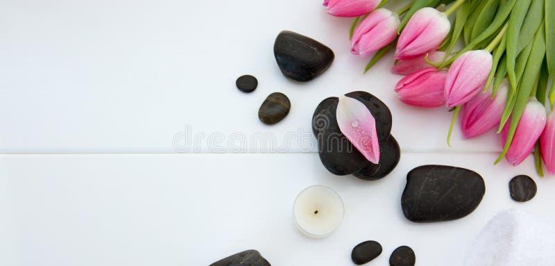 Spa inställning med tulpan, svarta stenar och handduken på vit träbakgrund fotografering för bildbyråer