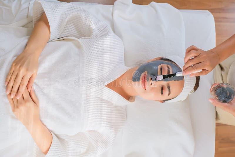 Spa kvinna som applicerar ansikts- behandlingar för leramaskeringsskönhet arkivbild