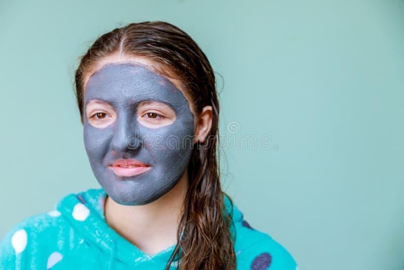 Spa kvinna som applicerar den ansikts- leramaskeringen Skönhetbehandlingar Närbildstående av den härliga flickan med en handduk p arkivfoton
