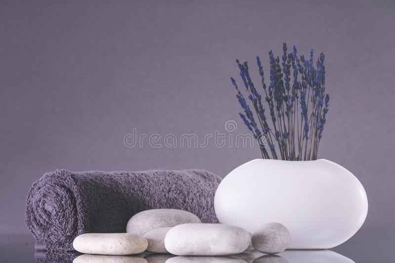 Spa. Lavender flowers stand in a white vase on a gray background. royalty free stock photo