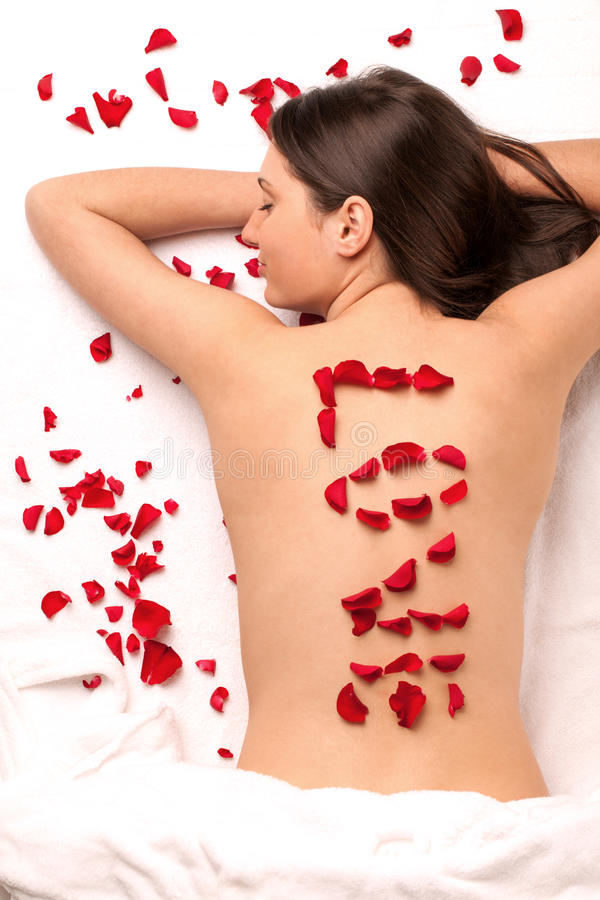 Spa lover. Girl with word LOVE on back made of rose petals stock photography