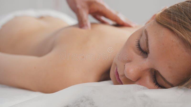 Spa Masaje para el modelo rubio de la mujer - sirva la mano del ` s en la parte posterior del ` s de la muchacha - ascendente cer imagen de archivo libre de regalías