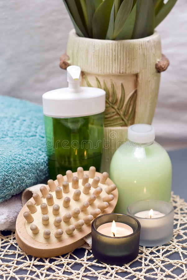 Spa massage and candles. Spa massage brush with candles and green fluid bottles. Green color composition royalty free stock photos