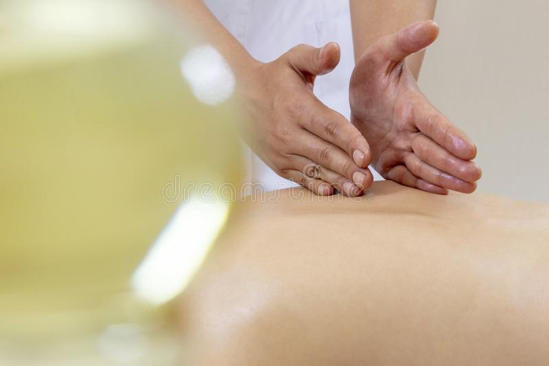 Spa massage. Female enjoying relaxing back massage in cosmetology spa centre. Body care, skin care, wellness, wellbeing, beauty tr. Eatment concept stock photography