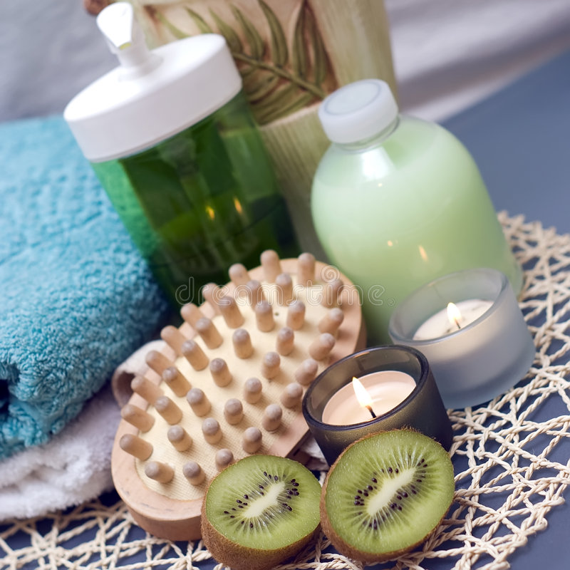 Spa massage and kiwi. Spa massage brush with candles and kiwi fruit. Green and blue composition royalty free stock images