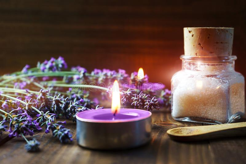 Spa massage setting with lavender flowers, scented aroma candles and cosmetic salt on wooden background royalty free stock images