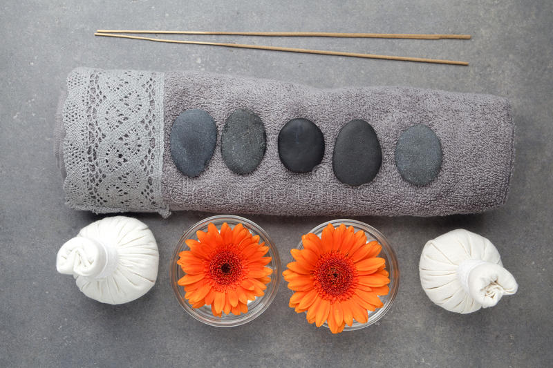 Spa massage setting with rolled towel, thai herbal compress balls and flowers. Flat lay. Top view. Spa massage setting with rolled towel, thai herbal compress royalty free stock photo
