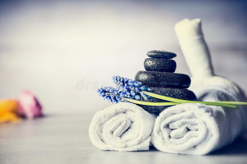 Spa massage setting with towels, hot stones and blue flowers, close up, wellness concept stock images