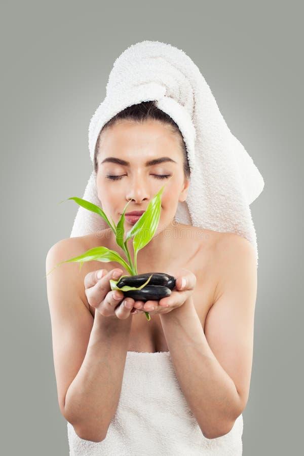 Spa modell Holding Green Bamboo och svartstenar fotografering för bildbyråer